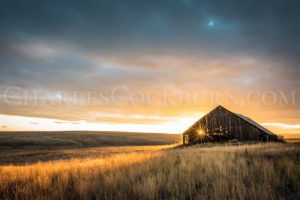 The setting sun sparkles through the crumbling wood of an ancient barn on the prairie near Douglas, Washington | CharlesCockburn.com