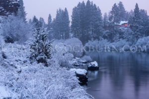 Snow gently blankets the shores of the Deschutes River in a peaceful winter calm